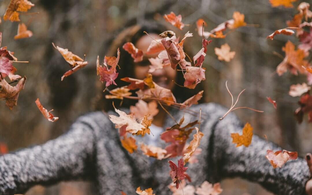 vrouw in bos gooit met herfstbladeren