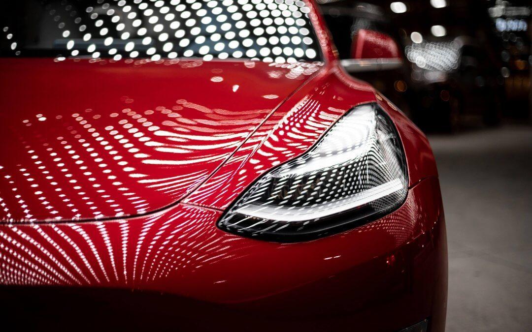 Rode Tesla waar op de motorkap en de voorruit de reflectie van wit licht op valt