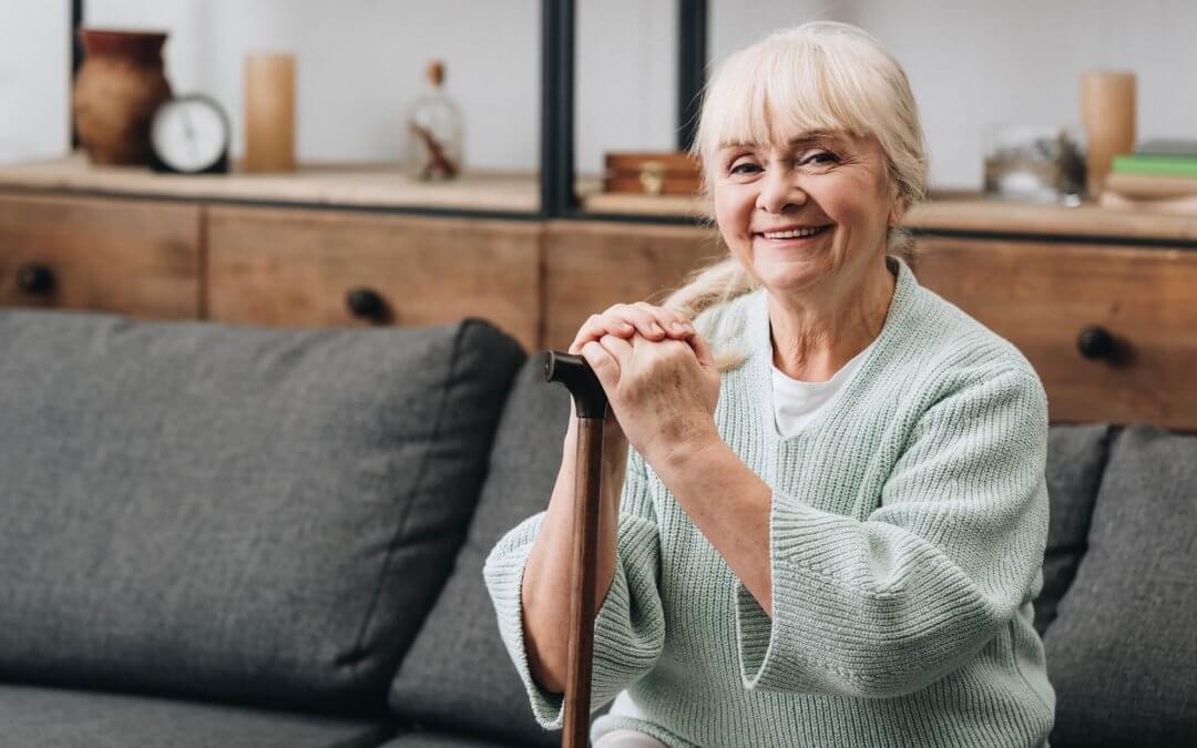 Oudere vrouw met een stok die zit op een bank