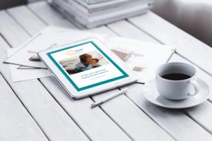 Tafel met witte planken met een kop koffie en een tablet met daarop het e-boek 8 tips voor gezonde bekkenbodemspieren door dr. Erna Beers