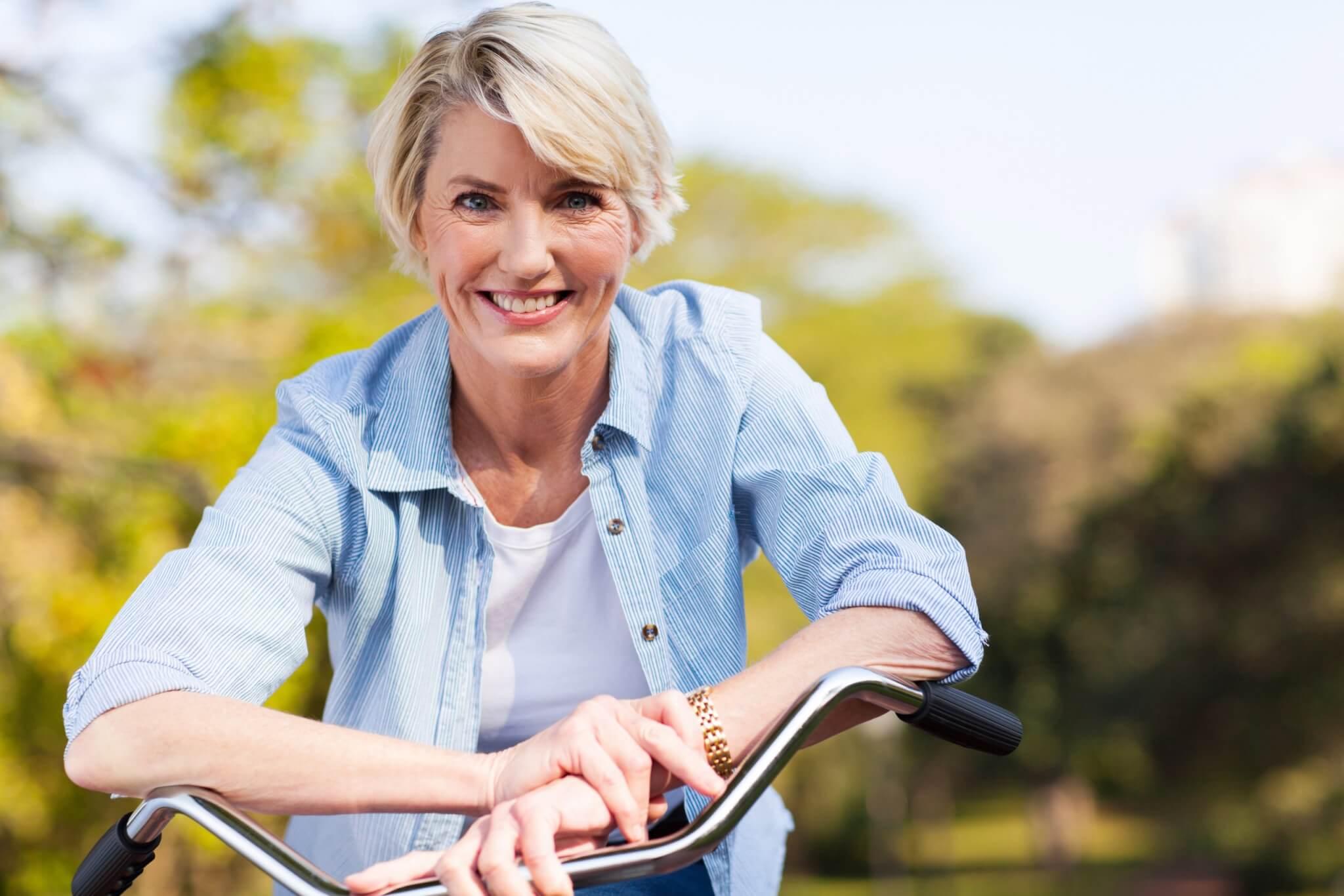 Blonde vrouw op een fiets die lacht omdat ze geen aandrang meer heeft